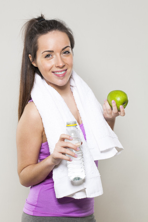 saludable: cute young fitness girl with white towel holding bottle of water and green apple as gym break Foto de archivo