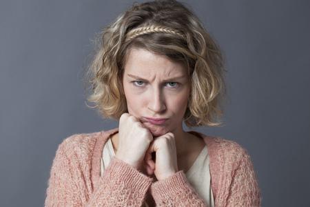 gefrustreerde jonge blonde vrouw gaan zitten mokken met vuisten onder de kin fronsen ogen in kinderlijke wijze