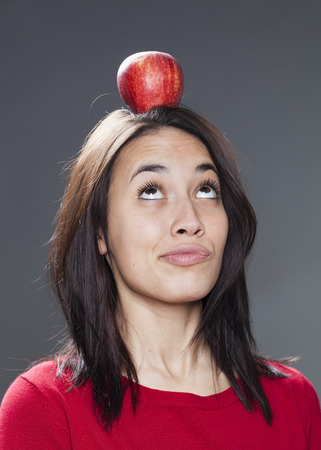 equilibrium: cute young brunette with red apple on top of head pouting for equilibrium and playfulness Stock Photo