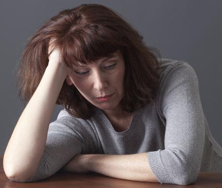Mujer mayor triste que se reclina la cara en sus manos que se establecen en una mesa para el aburrimiento o renuncia