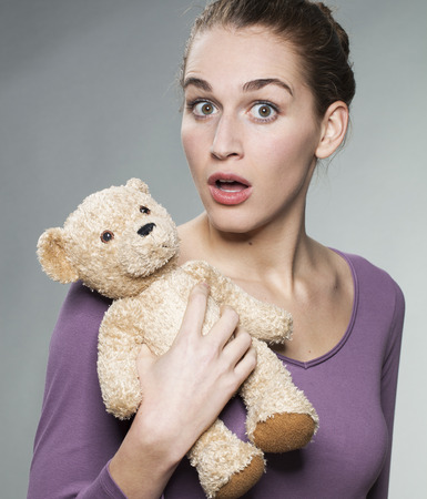 stunned: stunned young blonde woman hugging her teddy bear with tenderness for surprising child memories