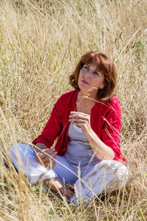 aging woman: female casual relaxation - sad aging woman sitting in long dry summer grass seeking for solitude and peaceful silence from the city,summer daylight