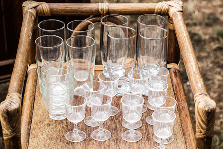 reusing: display of old crystal glasses and modern cheap glasses on wooden and ratan stool or table for presentation at garage sale for reusing or recycling objects Stock Photo
