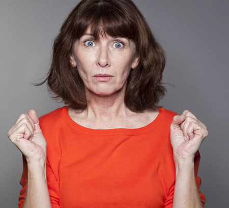 disappointed: surprise and disappointment concept - portrait of a senior brunette woman astonished and confused with hand gesture and eyes wide open,studio shot