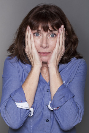 stressed out: fear concept - attractive mature woman hiding her cheeks with both hands looking anxious and stressed out with eyes wide opened,closeup in studio shot