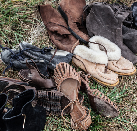 women in boots: mix of used leather women boots and shoes on sale at garage sale on grass for donation, recycling or selling for cheap to cope with over-consumption and fashion Stock Photo