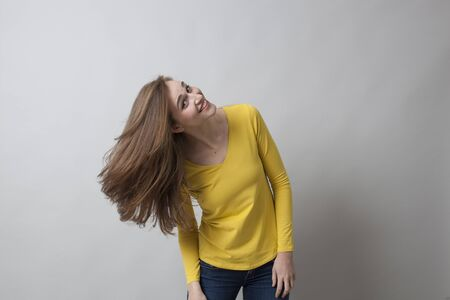 20's: cheeky beautiful 20s woman wearing yellow sweater and jeans, playing with her long hair for haircare with copy space