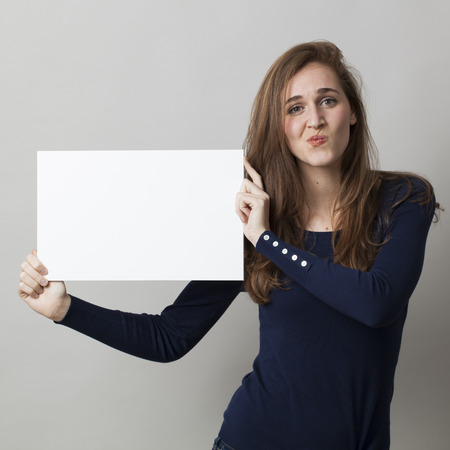 dubious: dubious young woman holding a message as scary communication Stock Photo