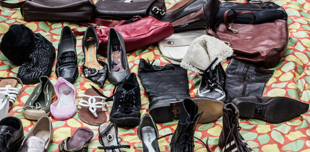 second hand: mix of second hand leather shoes, boots,purses and bags on sale at garage sale for donation, recycling or selling for cheap to cope with over-consumption