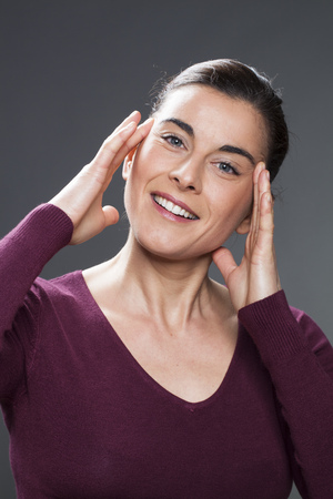 acupressure hands: glowing 30s woman smiling in practising face acupressure with hands on face and temples for natural eye care and facial contour exercise Stock Photo