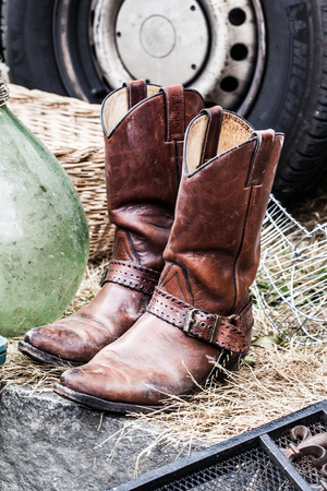 recycles: old leather cowboy boots on sale at garage sale for collection, welfare or selling for cheap to cope with over-consumption and fashion Stock Photo