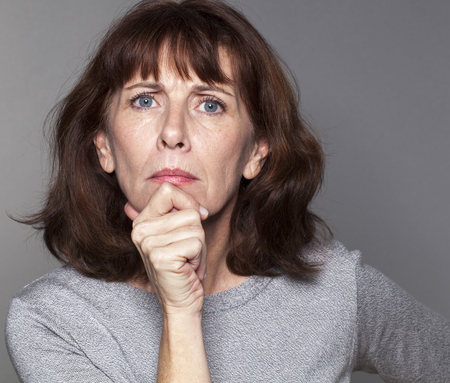 leant: frowning mature woman with brown hair and grey sweater thinking,face leant on hand,looking straight angry and disappointed