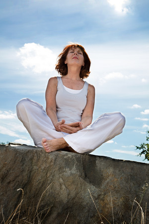 inner peace: senior zen - mature yoga woman sitting in relaxing position on a stone, seeking for harmony and inner peace outdoors,blue sky,low angle view