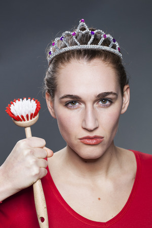 rebellion: young gorgeous woman wearing princess tiara with dish brush in hand for housekeeping queen or strong indignation against dirt