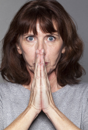 exasperation: closeup portrait of 50s woman under shock, praying for strength and success with both hands together in front of face