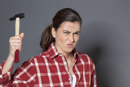 fed up: female DIY concept - unhappy young brunette woman holding hammer with violence,losing temper or fed up at having to work manually