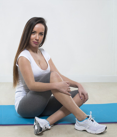 gym clothes: sexy young fitness woman sitting on an exercise mat with gym clothes ready for the class