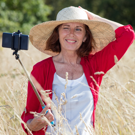 donne mature sexy: mature selfie concept - cheerful mature woman posing for selfie with a stick in summer dry meadows wearing a rural summer hat,natural daylight Archivio Fotografico