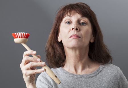 dubious: beautiful mature woman displaying dish brush as a house punishment for such a proud lady