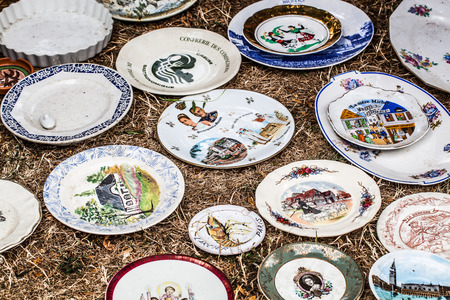 oldie: display of second hand or rustic plates with retro patterns and decors sold at flea market or garage sale for antique collection or collection fans Stock Photo