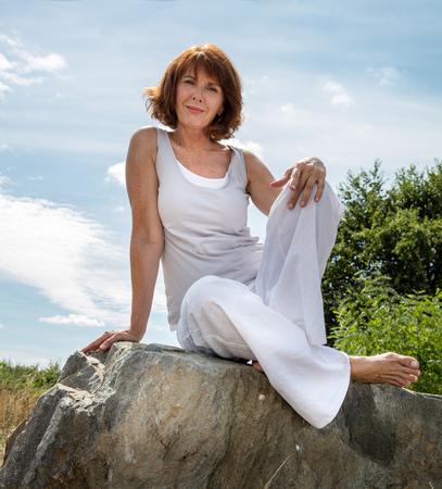 mujeres maduras: zen alto - sonriente, bellamente envejecimiento mujer sentada sobre una piedra para la sesión de yoga al aire libre vistiendo de blanco búsqueda de serenidad y bienestar en un parque, luz de día de verano