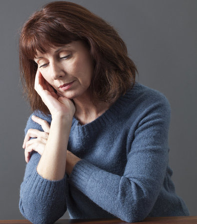 portrait of mature woman with brown hair and blue winter sweater thinking,face resting on hand,looking sad with distraught