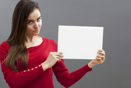 appealing: appealing young woman with a red sweater holding a blank message on board for seductive communication