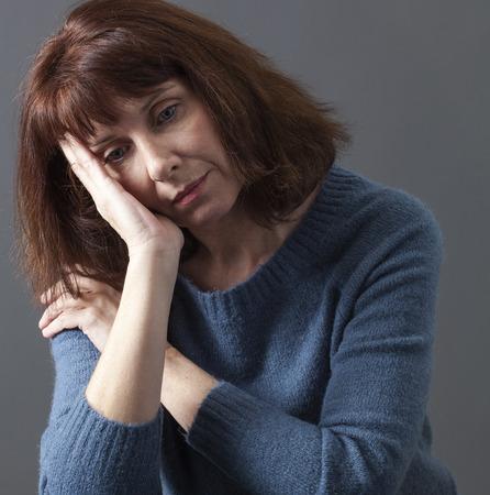 bezorgd 50's vrouw alleen met gezicht rusten op handen voor verdriet, reflectie of vermoeidheid als gevolg van de menopauze