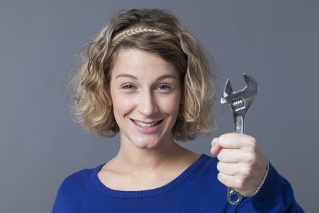 manual work: female DIY concept - happy young blond woman holding wrench or spanner with confidence and fun,enjoying manual work