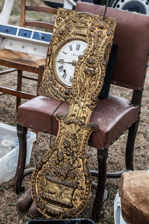 oldie: display of old clock parts in brass and rustic chairs sold at flea market for antique and vintage collections Stock Photo