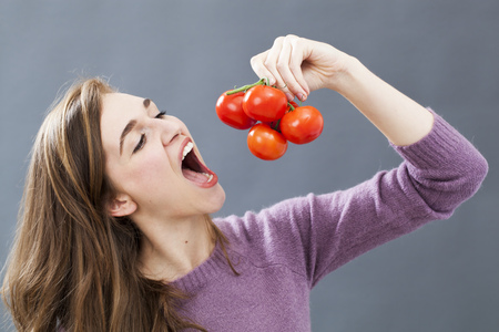 gorgeous young woman wanting to eat grape of tomatoes for veggie health and good appetite