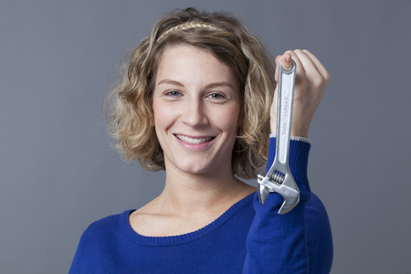 playfulness: female DIY concept - happy young blond woman holding wrench or spanner with playfulness for manual expertise Stock Photo