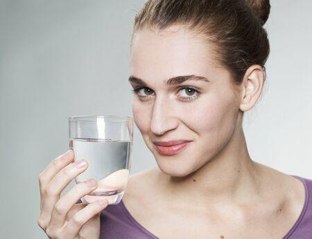 displaying: happy young beautiful woman wearing purple shirt displaying glass of pure tap water Stock Photo