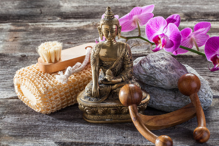 exfoliation: spa beauty treatment concept - washing-up, exfoliation and massage accessories with spiritual symbol such as Buddha on old wood and gray pebbles background for authentic body care decor