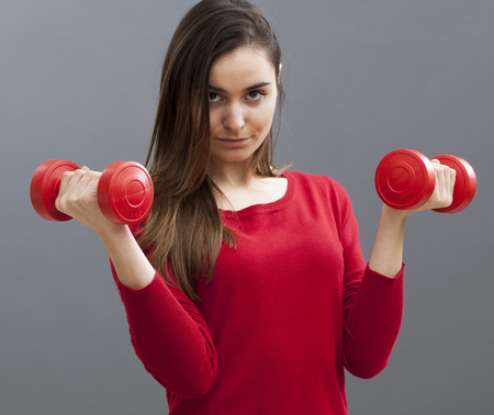 embarrassed: embarrassed athletic young woman wearing business clothes holding dumbbells for workout at the office Stock Photo