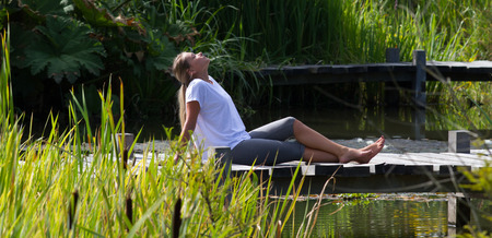 bare feet: relaxation outside - cool young woman with bare feet enjoying sun,lying on a wooden bridge with water and green environment, summer daylight