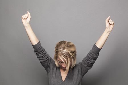 Concetto di successo - la giovane donna bionda di successo che vince una concorrenza con entrambe le mani si è alzata sopra con la testa in giù per il ringraziamento e l'umiltà Archivio Fotografico - 46963256