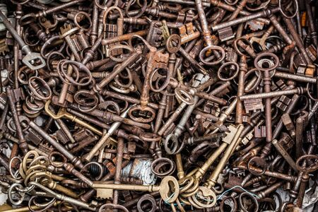 oldie: closeup of display of old rusted and brass keys in bulk for decoration or collection sold at flea market or garage sale for antique collection