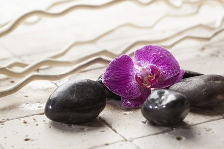 inner beauty: Black massage stones with flower and wood symbol for beauty
