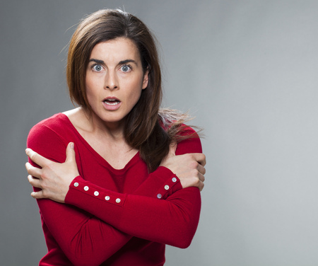 stunned: fear concept - stunned 30s woman with brown hair protecting herself with both hands on shoulders,studio shot Stock Photo