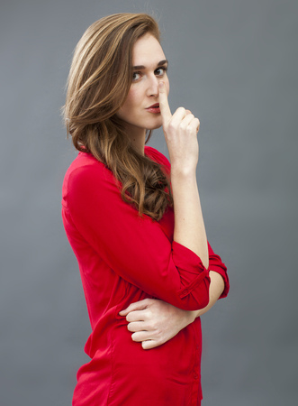 taboo: secret and taboo concept - mysterious 20s woman wearing red shirt asking for silence with finger on mouth,studio shot