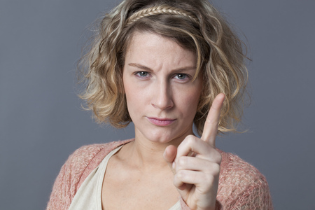 behaving: threatening 20s blonde girl showing her index finger for signal of stopping, forbidding or behaving with unhappiness