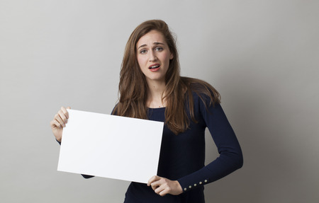 woman searching: young disappointed woman searching for a better answer with white board in her hands