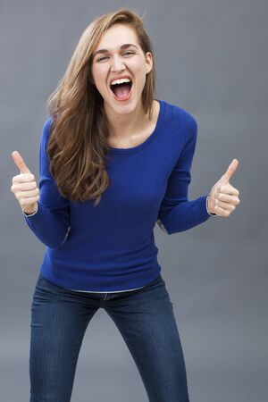 success concept - winning young woman wearing a blue sweater laughing with two thumbs up for victory