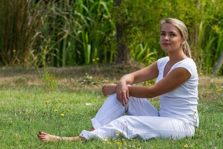 bare feet: relaxation outdoors - thinking young woman resting on grass with bare feet,green surrounding,summer daylight