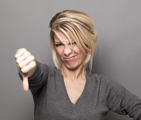 outraged: disappointment concept - offended young blond woman making a thumb down for disagreement or disgust