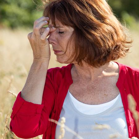 Hooikoorts allergieën - mooie veroudering vrouw met sinus pijn masseert haar neus tegen de hoofdpijn in droge weide, natuurlijke zomer daglicht Stockfoto