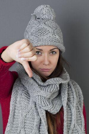 desilusion: concepto decepción - mujer joven decepcionado con sombrero de invierno y bufanda haciendo un pulgar hacia abajo para el desacuerdo o arrepentimiento