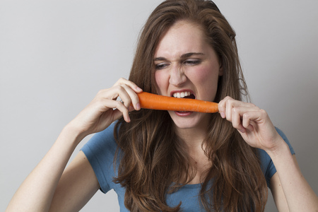 frustrating: young beautiful woman biting carrot with anger for frustrating diet
