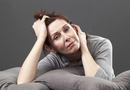 moe senior vrouw die haar gezicht en handen vaststelling op kussens voor comfort en ontspanning Stockfoto